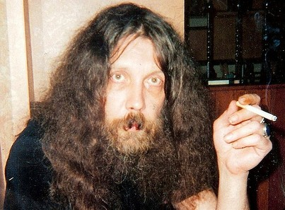 Alan Moore smoking a cigarette in a pizza restaurant in Northampton in 1998