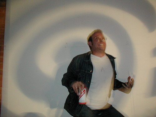 Man dancing at Idler party in the stupid Nineties with a snail projection behind him