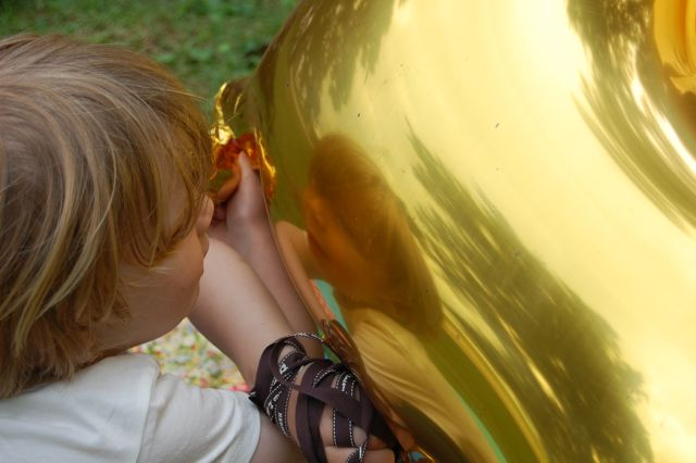 Child gazing into golden horse balloon