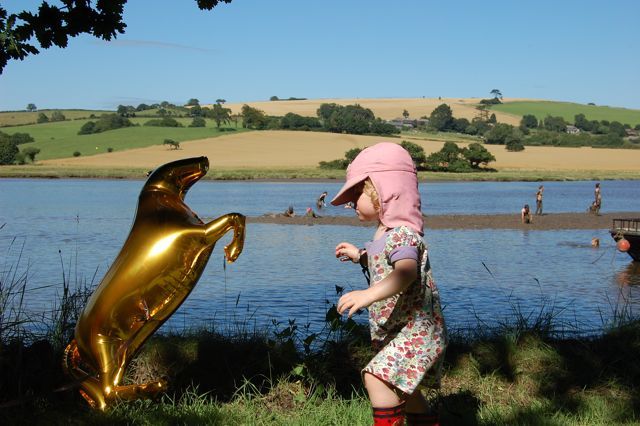 child with golden horse balloon beside a river